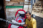 Portrait of Ivan (26) with his new born son Kristian in front of their hut at the Roma settlement in Ostrovany.