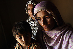 "Sisters, left to right, Zubada and Tasleem, holding daughter Rafiabibi, 6, Dera, Pakistan, April 26, 2004. They talk about their horrible experience of being gang raped by neighbors who felt they were dishonored by Zubada's son Naeem. Members of the Human Rights Commission in Multan, including social worker Asia Perveen, are working with the women to get them legal representation so they can fight the accusers in court. ""I want them to be punished,"" said Tasleem. ""They are our enemies, I will be afraid until they are hanged publicly."" Until now, the accused rapists are still at large."
