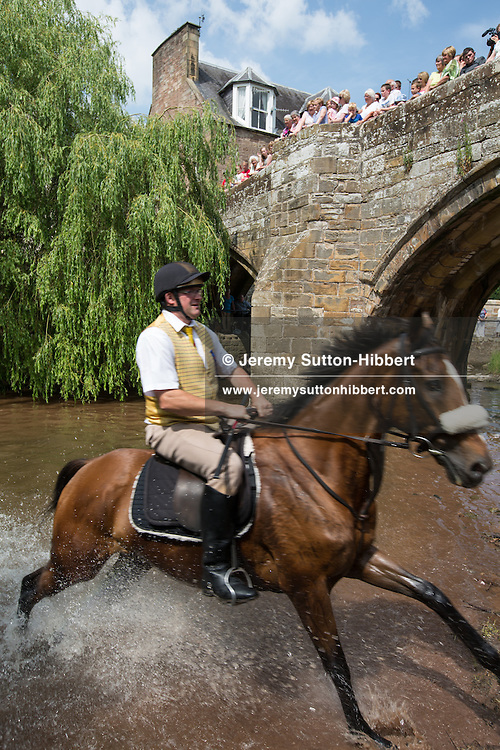 The Jed River is forded at Auld Brig, Jethart Callant's Festival, in Jedburgh,  Scotland, Friday 12th July 2013. With Callant Garry Ramsay, Right Hand man Iain Chisholm, Left Hand Man Ryan Miller, and Herald Allan Learmonth.<br /> N55&deg;28.672'<br /> W2&deg;33.067'