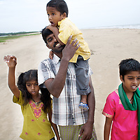 Viswanathan walks with his son Sanjay and daughters Vijyashree (left) and Vijitha on the beach close to the location of his wife's death in the tsunami. ..Vijitha and Vijyashree Viswanathan, now age 13 and 11, lost their mother and younger brother to the 2004 Asian Tsunami. The sisters continue to live with their father Viswanathan in a small house in the fishing village of Thalanguda, 5km from Cuddalore. The house does not have a toilet and water is supplied for only a short period of the day. Viswanathan married Kayalvizhi just over a year after the tsunami and the couple now have a son Sanjay, born December 2006 and daughter, Monica, born September 2008. ..Vijitha and Vijyashree continue to be close to their father who admits to feelings of guilt about his re-marriage. Viswanathan shows all of his children more attention than the average father in a patriachal south Indian fishing village. With little opportunity to reminisce for the past, Vijitha and Vijyashree have got on with their lives and appear relatively content. They both rely on each other for support and enjoy the reassuring company of their paternal aunt Shanti who lives in a neighbouring house. Shanti accuses Kayalvizhi of being indifferent to the needs of her adopted daughters and forcing them to undertake too many household chores. Shanti is pursuing the idea of having Vijita and Vijyashree live with their maternal grandmother where she feels their mother's extended family would be more attentive to the girls' needs. On holidays the sisters have the opportunity to visit their maternal grandmother Govindamal who lives in the neighbouring district of Nagapattinam. Both Vijitha and Vijyashree continue to pursue their studies at Thalanguda government school. ..Photo: Tom Pietrasik.Cuddalore, Tamil Nadu, India.November 23rd 2008..THIS PHOTOGRAPH IS THE COPYRIGHT OF TOM PIETRASIK. THE PHOTOGRAPH MAY NOT BE REPRODUCED IN ANY FORM OTHER THAN THAT FOR WHICH PERMISSION WAS GRANTED. THE PHOTOGRAPH MAY NOT BE