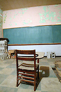 A lone desk sits before a chalk board in a 100-year-old school in Andover, South Dakota.  The school has been closed for nearly 50 years.