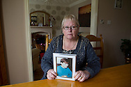 Margaret Lewis, pictured at her home in Kirkby, Liverpool holding a photograph of her deceased son, Carl. Mrs Lewis faces the prospect of having to pay additional money for rent with the introduction of the so-called Bedroom Tax, which comes into effect in April 2013. She lost her son Carl, then 18, at the Hillsborough football stadium disaster in 1989 and may have to move to a smaller property than the one in which she brought up her son. The street which she lives was renamed in Carl's honour around 15 years ago.