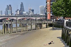 June 19, 2017 - London, UK - London, UK. A woman sunbathes on the bank of the River Thames on the exposed beach at low tide during hot weather where temperatures in the capital are 30C.  More hot weather is expected in the next few days. (Credit Image: © Stephen Chung/London News Pictures via ZUMA Wire)
