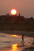Newport, RI 2006 - Girl plays in shallow water at second beach in the glare of the sunset reflecting off the wet sand.