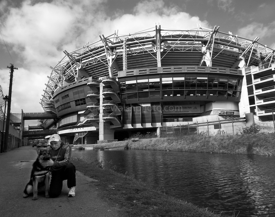 "It's a Friday afternoon. I'm down beside the Royal Canal, taking photos of Croke Park, the Irish gaelic sports stadium. ..A bloke with a dog walks past. ..""Hey mister, can you take pictures of dogs with that camera?""..""Uh, yeah, I could, I suppose""..""Can you take a picture of Max? He's only seven months old, and me last dog was killed by a car.""..""Ah. My sister's dog was killed by a car two weeks ago. Staffy-whippet cross""..""Right. Very intelligent then"", taps his head, meaninfully...I get him to write down his address. Hey gets a bit confused doing it. ..""Sorry man, I had a big operation on my head, and I get mixed  up"", takes off his baseball cap, shows me criss-cross collection of scars all over his crown and down to his chin. ..When I got Richie and max to stay still long enough, I managed to get some photos. I'm posting them to Richie. Hope he puts them on his wall.."