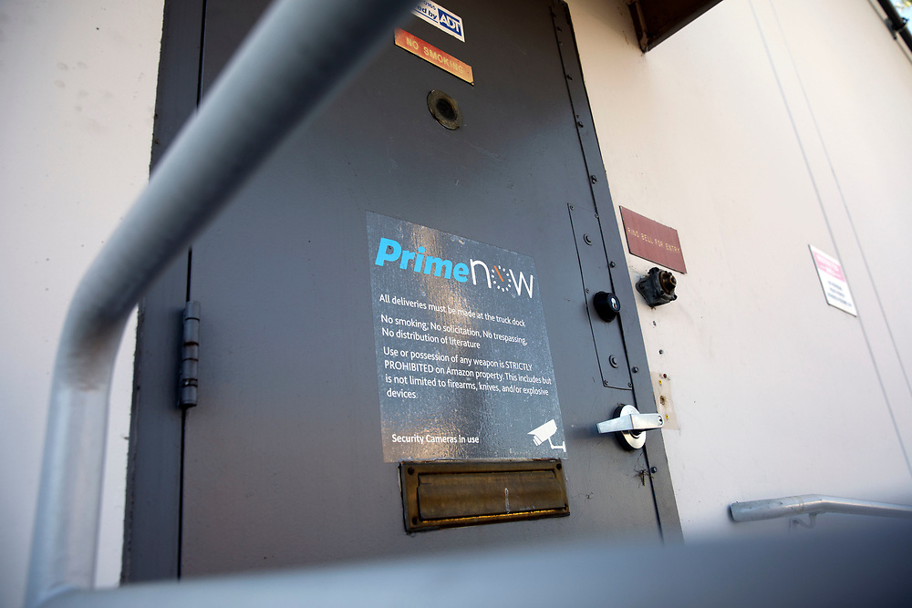 The Amazon Prime Now logo is displayed on a door at the Amazon.com Inc. Prime Now fulfillment center warehouse on Monday, March 27, 2017 in Los Angeles, Calif. The warehouse can fulfill one and two hour delivery to customers. Complex supply chains such as Amazon's and e-commerce trends will impact city infrastructure and how things move through cities. © 2017 Patrick T. Fallon