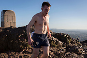 """A runner reaches the summit of Arthur's Seat in Holyrood Park, overlooking the city of Edinburgh, on 26th June 2019, in Edinburgh, Scotland. Arthur's Seat is an extinct volcano which is considered the main peak of the group of hills in Edinburgh, Scotland, which form most of Holyrood Park, described by Robert Louis Stevenson as """"a hill for magnitude, a mountain in virtue of its bold design"""". The hill rises above the city to a height of 250.5 m (822 ft), providing excellent panoramic views of the city and beyond."""