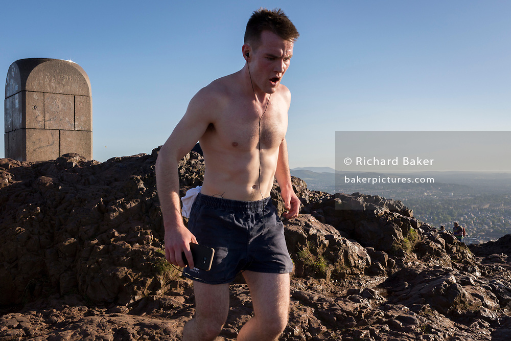 "A runner reaches the summit of Arthur's Seat in Holyrood Park, overlooking the city of Edinburgh, on 26th June 2019, in Edinburgh, Scotland. Arthur's Seat is an extinct volcano which is considered the main peak of the group of hills in Edinburgh, Scotland, which form most of Holyrood Park, described by Robert Louis Stevenson as ""a hill for magnitude, a mountain in virtue of its bold design"". The hill rises above the city to a height of 250.5 m (822 ft), providing excellent panoramic views of the city and beyond."