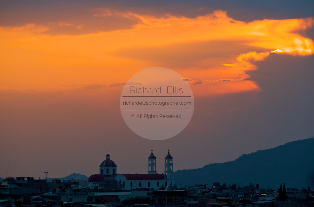 Sunset over the Iglesia de Nuestra Church in Zitacuaro Mexico in central Mexico state of Michoacan. Zitacuaro is the entry city to the Monarch Butterfly Biosphere Reserves . Each year hundreds of millions Monarch butterflies mass migrate from the U.S. and Canada to Oyamel fir forests in the volcanic highlands of central Mexico. North American monarchs are the only butterflies that make such a massive journey—up to 3,000 miles (4,828 kilometers).