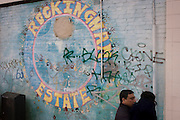 Street mural landscape and local man on the Rockingham Estate in the London borough of Southwark, England. The man carries a young girl in his arms, its face unseen to the viewer. Graffiti has been sprayed on the brickwaork where the mural has been painted near a junction and on the wall of a corner community shop. Rockingham is located in south London near the Elephant and Castle. Notorious for youth issues including gangs and knife crime where 12-year-olds are seen holding knives in broad daylight. For families with young children this would be an intimidating community in which to live.