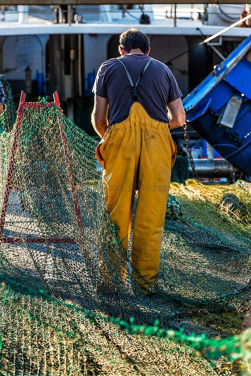 Young fisherman mending fishing nets, Palamos, Spain