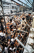 Vietnamese men try to scale walls of American Embassy in saigon during the Fall of Saigon, Vietnam