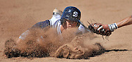 Brandon Trinkwon of Beckman gets a face full of dirt as he slides safe into third base as Warren's Rey Sanchez dives to try and make the tag during Thursday's playoff game.