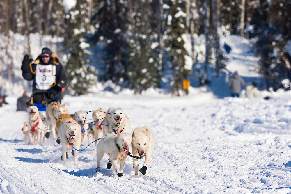 Musher Jim Lanier competing in the 40th Iditarod Trail Sled Dog Race on Long Lake after leaving the Willow Lake area at the restart in Southcentral Alaska. Afternoon. Winter.