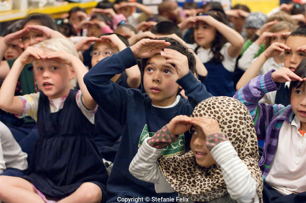 Kindergarteners sing together and act out songs with hand movements
