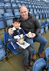 Pictured: 9 year old Joshua Holt with his dad Kenny looking forward to the match at Falkirk.<br /> <br /> How many Scottish football fans promise themselves a trip to every senior football ground in the country sometime in their life? Probably the majority when they retire.  One such fan who decided to get that milestone ticked off early in his life is nine year old Joshua Holt, from Edinburgh and an Edinburgh City fan, who completed his tour on Saturday 30 December at the Falkirk Stadium when Queen of the South are the visitors.  It has taken four years for Joshua, accompanied by his father Kenny, to complete the tour which started off on 31 August 2013 at Ibrox when Rangers took on East Fife.  A goal feast was on offer that day as Rangers won 5-0 but Joshua, like most five year olds, was more interested in everything else that accompanies a trip to one of the biggest stadiums in the UK.  His father, however, noticed a lot more than the football on the pitch; he had discovered what his football had been missing – a like minded companion.  This was their 'thing' to do together; father and son; come rain or shine.  Not the 'quality time' so often quoted as an essential for a parent but real time doing something they both enjoy.  A shared experience can build stronger bonds than any amount of treats from father to son.  They have travelled over five and a half thousand miles on their long journey and have enjoyed an average 2.9 goals per game.  Not a bad return for the commitment they have shown.<br /> <br /> Fans on match days have their own rituals, be it their lucky scarf; same bus for away games; or heading to the same seat for home games.  Joshua and Kenny go for the four Ps; popcorn, pin badge, programme and pie.  Popcorn for the trip to the ground with the programme and pin badges bought from the club shop as a reminder of the visit.  The catering is always tested especially on these cold days.  For the record Joshua can't see past a Dunfermline pie but his dad prefers a R