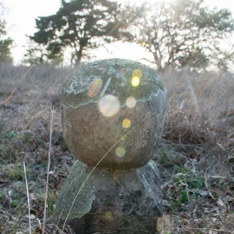 The Cedar Creek Cemetery was home to some very unique head stones. This head stone is a ball made of concrete placed on an obelisk pedestal. Over the years, a green fungus has started to cover the top.