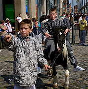 Editorial Only. The horse market at Smithfield, Dublin takes place on the first Sunday of every month. People come from all over Ireland to trade horses and equipment. It's absolute chaos, with young kids galloping across the cobbles on distressed looking ponies, horses whinnying, gardai chasing jaunting cars on their bicycles. A big part of the horse scene involves the keeping of animals, by Dublin urban youth, in gardens or public areas. The Dublin Society for Prevention of Cruelty to Animals says that the market facilitates the sale of horses to under-16s, who are then unable - or unwilling to look after them. Amongst the dozens of horses visible, I did see a couple of examples of cruelty - the most obvious one of all was by an elderly man, kicking his pony in the stomach for no apparent reason. ....There's talks by Dublin City Council of moving the market out of the city - as Smithfield becomes increasingly gentrified, the more urbane of the urban dwellers in the surrounding apartments are apparently unimpresssed with the smell of horse shit once a month!....Editorial Use only