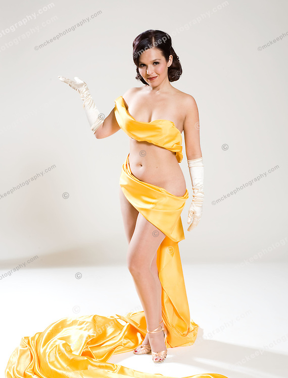 Young woman wrapped only in gold cloth, coyly looking at the camera.
