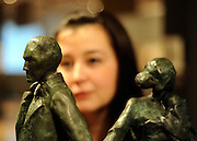 ©London News pictures. 07.02.2011. Penny Day, Head of Irish Art at Bonhams, looks at  a sculpture by Eamonn O'Doherty (Irish, born 1939) Emigrants 48 cm. (19 in.) high Estimate: £3,000 - 5,000. Irish Art on display at Boham's today (07/02/11) ahead of its sale. Highlights include a portrait of Francis Bacon, one of Britain's leading 20th century artists, painted by one of his friends, Louis Le Brocquy. The watercolour, titled Image of Francis Bacon No 18, is estimated to sell for £60,000 to £80,000. The sale is held on February 8th. Bonhams, 101 New Bond Street, London, UK.. Picture Credit should read Stephen Simpson/LNP