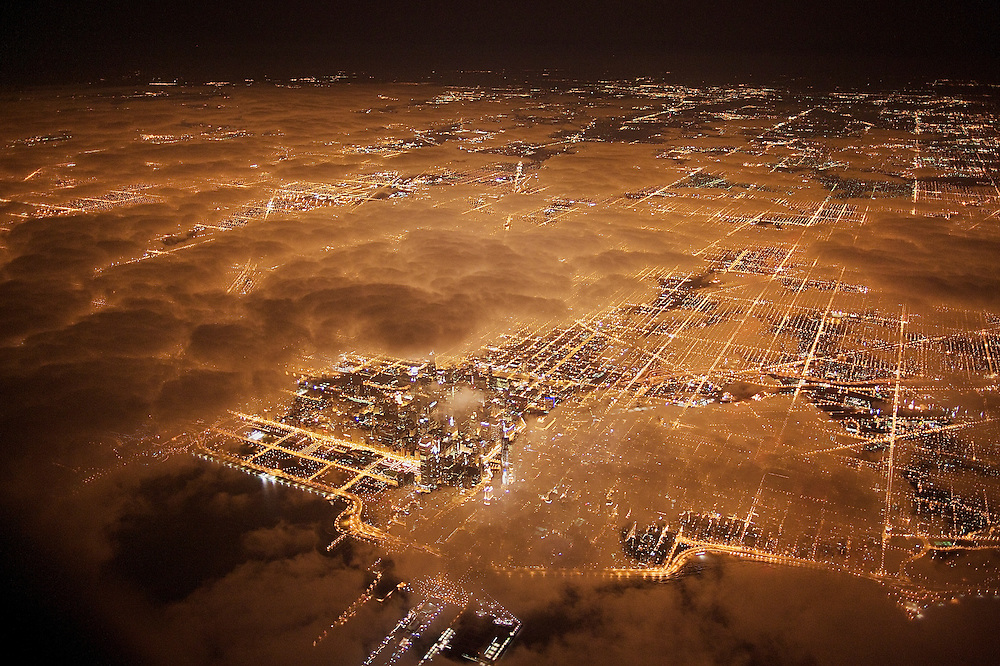Chicago glows in the night as clouds drift in off the lake.  The cities pattern of streets, which shows up so distinctly at night, is unusually rigid and the core city area is lit almost entirely with sodium vapor lamps.