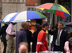 The Great British Summer, raining in August people running from the rain outside Liverpool St Station, August 8, 2000..Photo by Andrew Parsons/i-Images..