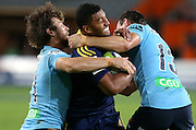 Highlanders Lima Sopoaga, centre, in the tackle of Waratahs Rob Horne, left, and Matt Carraro in the Super 15 rugby match, Forsyth Barr Stadium, Dunedin, New Zealand, Saturday, March 14, 2015. Credit: SNPA/Dianne Manson