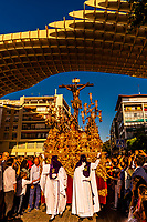 Hooded Penitents (Nazarenos) and a paso (float) of The Crucifixion of Jesus Christ in the procession of the Brotherhood (Hermandad) San Benito pass the Las Setas (Metropol Parasol), a wooden structure, Holy Week (Semana Santa), Seville, Andalusia, Spain.
