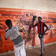 Moment d'entraînent de takwondoo au Centre Socio Culturel de Thiaroye sur Mer; sur le mur la peinture d'une scène symbolique, avec les pirogues qui ont marqué la vie de Thiaroye, pour la pêche et pas seulement