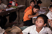 A student at The Ban Buamlao Primary School in Ban Buamlao, Laos, appears to be in thought.  According to the 4 faculty members, many of the 120 students who attend the school each day want to continue to high school and college. Grades 7 through 12 will cost each student about $60 USD (United States of America dollars) per year, but college will be approximately $100 USD annually.