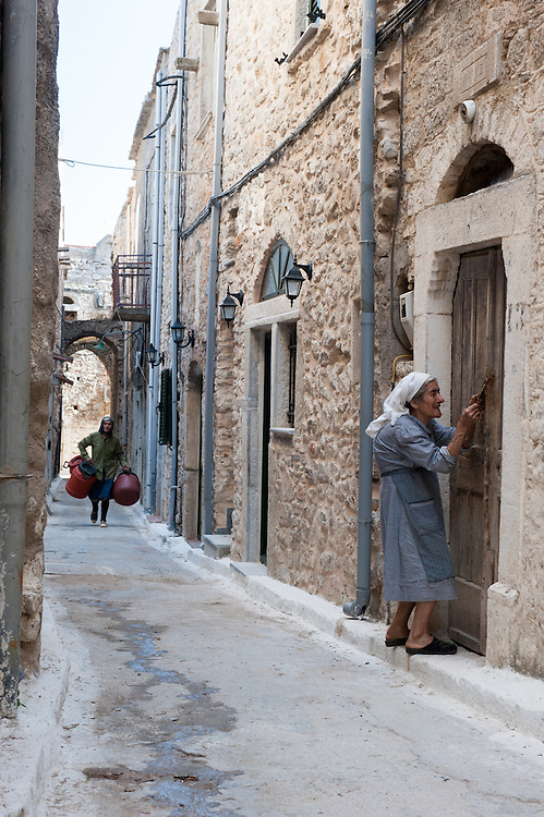 An elderly woman entering her old house in an alley in the medieval village of Pyrgi, Chios, Greece. <br /> <br /> Pyrgi in Chios is known as the &quot;painted village&quot; on account of the decoration of the houses. The village still keeps its medieval style and together with the other Mastichochoria (Mastic Villages) are in the list of the Intangible Cultural Heritage of Humanity of UNESCO