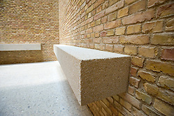 Simple stone bench  seaating and brick wall within Egyptian courtyard room of newly renovated Neues Museum in Berlin 2009 Architect David Chipperfield