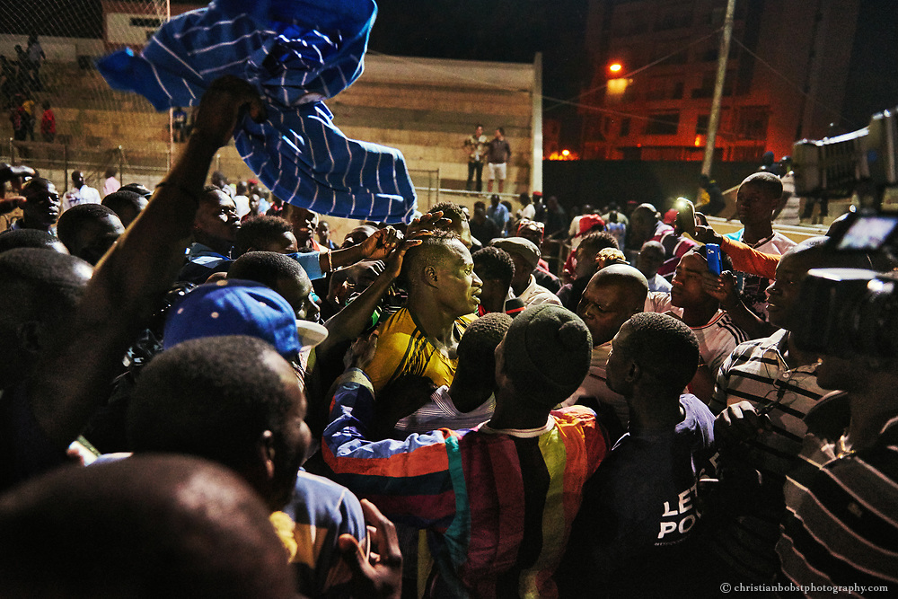 The audience and press storm the arena after the final fight to celebrate the winner, as here in the Iba Mar Diop stadium in Dakar, March 29, 2015. The winner can count himself happy; nevertheless, he has just won prize money worth 7000 dollars - in Senegal a lot of money.