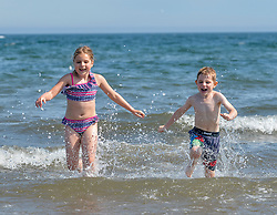 Brother and sister Niamh Leslie (10) and Arran Leslie (5) from Edinburgh, cool down in the sea at Portobello on what is predicted to be the hottest day of the year.<br /> <br /> © Dave Johnston / EEm