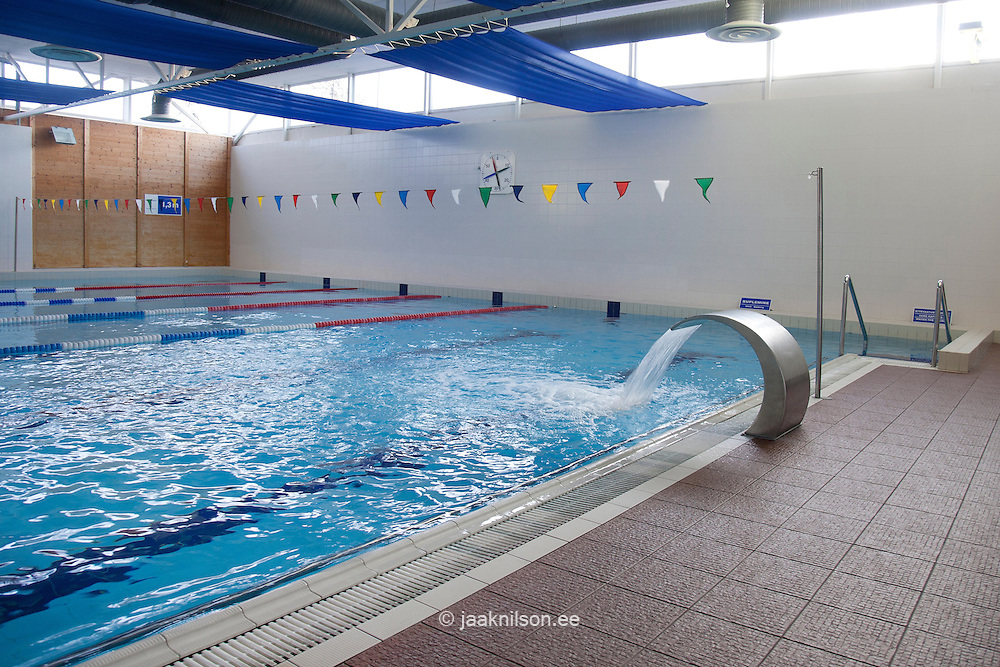 Indoor swimming pool with water shute and curved metallic shape with flowing water in Viimsi Spa Hotel in Tallinn, Estonia