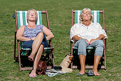 © Licensed to London News Pictures. 22/08/2015. London, UK. Two women sunbathing on deckchairs in Green Park. Photo credit: Pete Maclaine/LNP