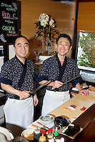 Portrait of Asian chefs preparing sushi together
