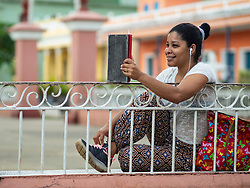 North America, Caribbean, Cuba, Remedios, teen talking on mobile phone in plaza