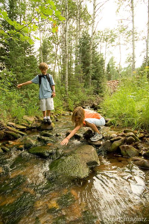 family hiking along stream