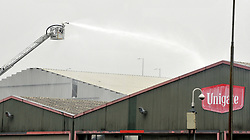 © Licensed to London News Pictures. 31/01/2012, London, UK. Fire crews used remote platforms to control the fire. A huge fire, thought to be in an old dairy building containing small business is causing road and tube closures in Wood Lane, West London today 31 January 2012.  A large number of Fire Brigade and London Ambulance are in attendance. Photo credit : Stephen Simpson/LNP