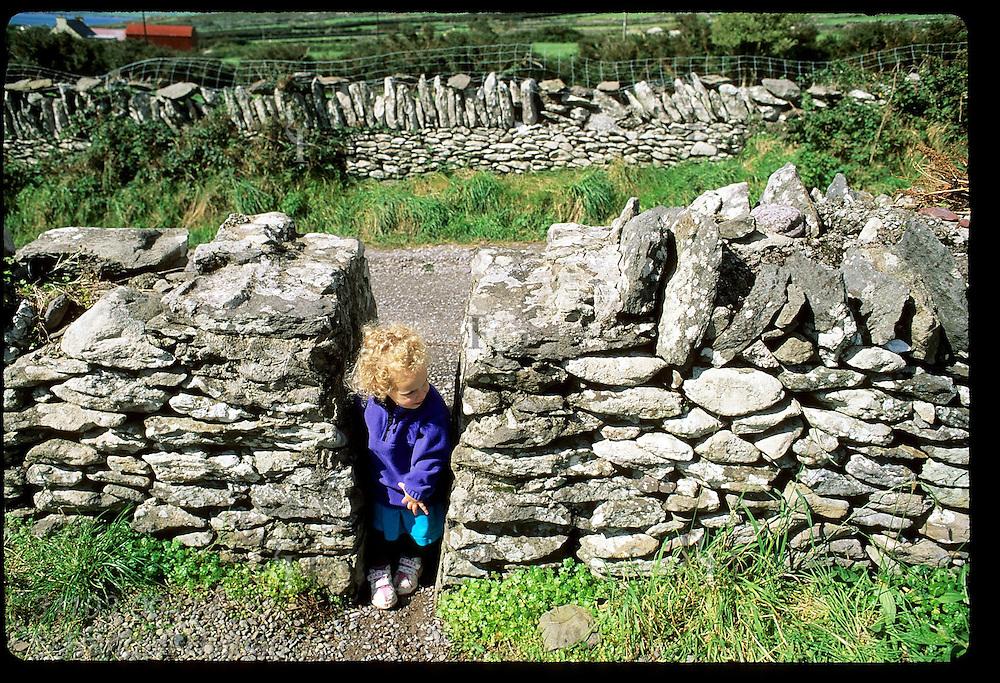Little girl peeks between stone walls in cemetery at Kilmalkedar Church on the Dingle Peninsula; southwest Ireland.