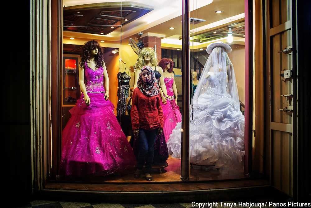 A young fiancee goes wedding dress shopping in Gaza. Her future husband is working in Libya, where she hopes to join him. Since the Israeli siege, many Gazans say that girls are marrying younger as there are now fewer possibilities for both work and travel. Most young girls say they hope to find a husband who is based outside or will find work that will take them away from the confines of Gaza.