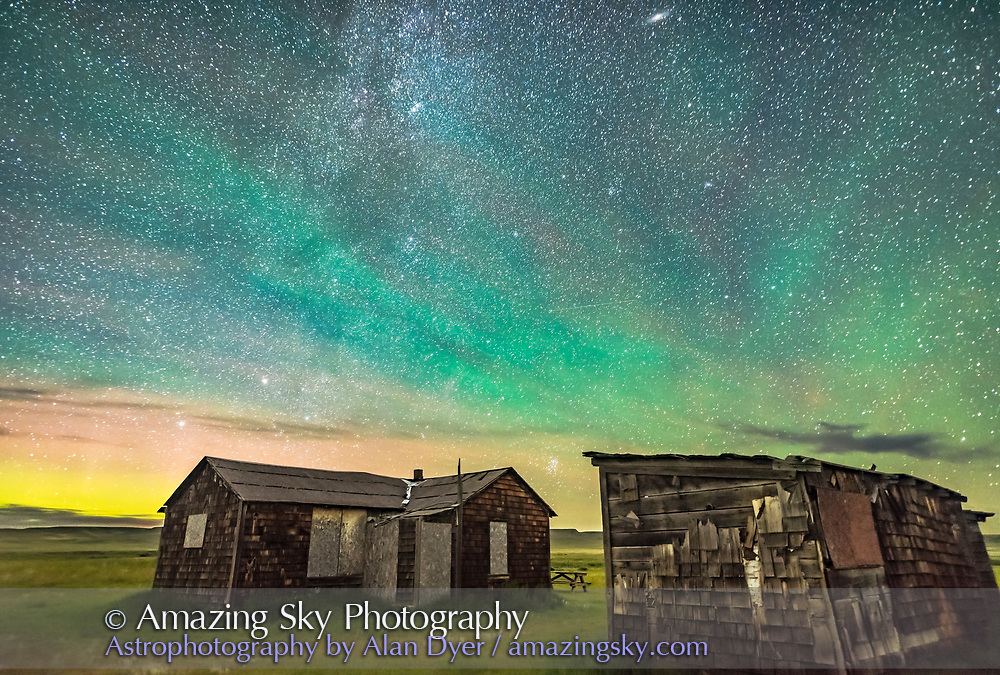 The Pleiades rising behind the rustic cabins and outbuildings of the historic Larson Ranch in Grasslands National Park, Saskatchewan. Aurora shines to the left in the north while green airglow illuminates the sky to the east above the buildings. Grasslands is a Dark Sky Preserve. And the sky is very dark. All illumination here is natural &mdash; note the dark clouds seen against the brighter airglow-lit sky. <br /><br />This is a stack of 4 exposures for the ground to smooth noise and one exposure for the sky, all untracked, and 30 seconds at f/2 with the 20mm Sigma lens and Nikon D750 at ISO 3200.