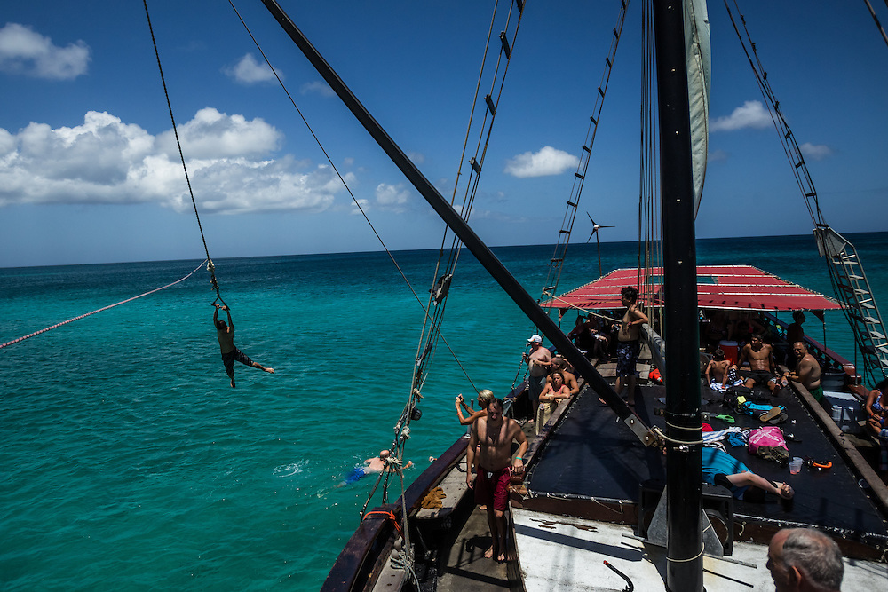 ARUBA- Tourists enjoy a rope swing on a sailboat during a snorkeling tour. Aruba is a 20-by-6-mile southern Caribbean island with white sand beaches, and is as multicultural as the United Nations, with a population of about 109,000. PHOTO: Meridith Kohut for The New York Times