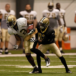 08 August 2009: Receiver Marques Colston (12) runs after a catch as cornerback Tracy Porter (22) attempts the tackle during the New Orleans Saints annual training camp Black and Gold scrimmage held at the team's indoor practice facility in Metairie, Louisiana.