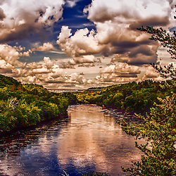 The kettle river train bridge in Sandstone Minnesota. A train is on the bridge, the river was flooded and the sky was active.