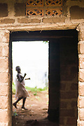 A pygmy girl displaced from the Bwindi forest plays near a home a local NGO is building for a resident teacher.