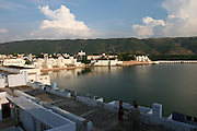 An overview of the lake and town center in Pushkar, Rajasthan, India. Every year in November thousands of Rajasthani tribal people converge in the picturesque town of Pushkar, which is also a major site for Hindu pilgrims. They come to buy and sell camels (over 50,000) and other cattle and bathe at the Pushkar lake (considered sacred by Hindus). They come for the entertaining camel races and local circuses, and to browse the local markets for camel saddles, textiles, glass bangles and silver jewelry..Photo by Suzanne Lee