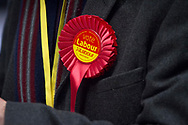 A Labour Party supporter with a red rosette at Bidston Tennis Centre, Wirral during the counting for the Wirral West constituency in the 2015 UK General Election. The constituency was held by Esther McVey for the Conservative Party, who won the seat from Labour at the 2010 General Election. The constituency was one of the key marginal seats contested between the two main UK political parties and was won by the Labour Party.