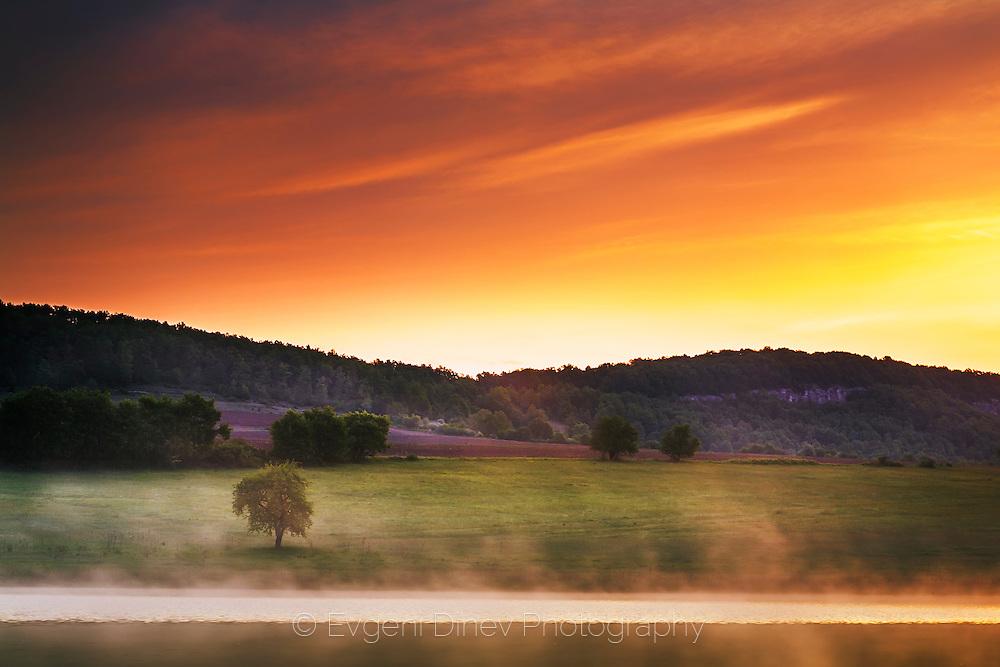 Sunrise by the misty lake